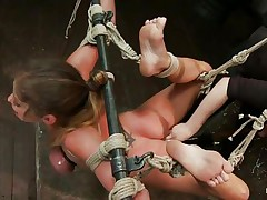 Sexy milf brunette's hands and legs are bound and suspended bare in the air. Her oily boobs are also tied. Her legs are made widened so that the girl can easily permeate in her pussy. She put her fingers deep in brunette's cunt.