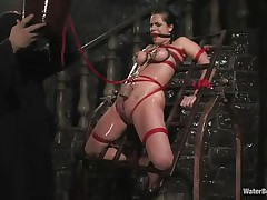 Mia Bangg is bound and gagged in the dungeon where her torturer sprays her nipple-clamped tits. He asks if this babe wants to get fucked and this babe does, but first he gives her a little greater amount pain by pulling tight the rope that splits her pussy lips and smacks her pussy before using a dildo on her.