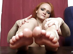 This woman really wants to wrap her feet around a cock and make it cum, but unfortunately this babe does not have a cock handily available. Therefore, this babe is making use of the next superlatively good thing, which is a nasty big dark vibrator standing up right on the table. She is caressing that with her feet.
