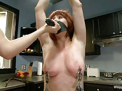 Odille has a strap on dildo attached on her face and with her hands bound and clamps on her nipples and pussy that babe waits patiently in the kitchen for the blond milf to undress. After the blond is naked, with a little aid and guidance that babe insets the dildo in that shaved cunt, fucking it like a submissive slut.