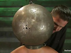 Adrianna Luna has her legs held apart by a support and her hands are encased by metal balls. Her head is encased by a metal ball as well and pumps on her nipples. She acquires a sex tool on her cunt and acquires the okay to cum. Then she's tied to a table and having clamps put on her cunt and tits. Freaky!