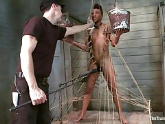 Nikki is all tied up and standing on her legs. Filled with clothespins and strings, she has to be careful and not to drop the two buckets she`s holding, while a big vibrator makes sensations on her wet cunt. This babe acquires all whipped for being such a bad ebon girl. Her executor will take very admirable care of her!