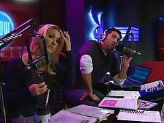 The hosts of Playboy Radio's Morning Show are looking at their guest model who is wearing the suit she'll be wearing to the Playboy Mansion for Halloween. Her head and love muffins are covered in fake fruit like oranges, limes, lemons, and more. She flashes her breasts for the hosts and viewers.